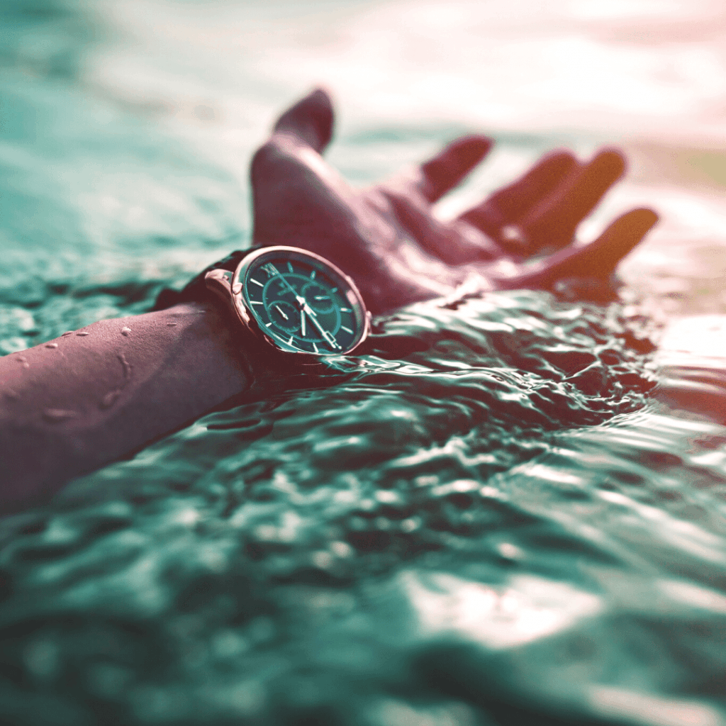 Photo of a watch on a mans wrist over a body of water.
